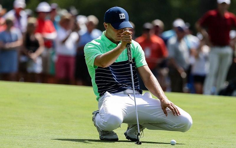 En premier, il tente de déterminer la ligne du putt depuis une position derrière la balle vers le trou.
