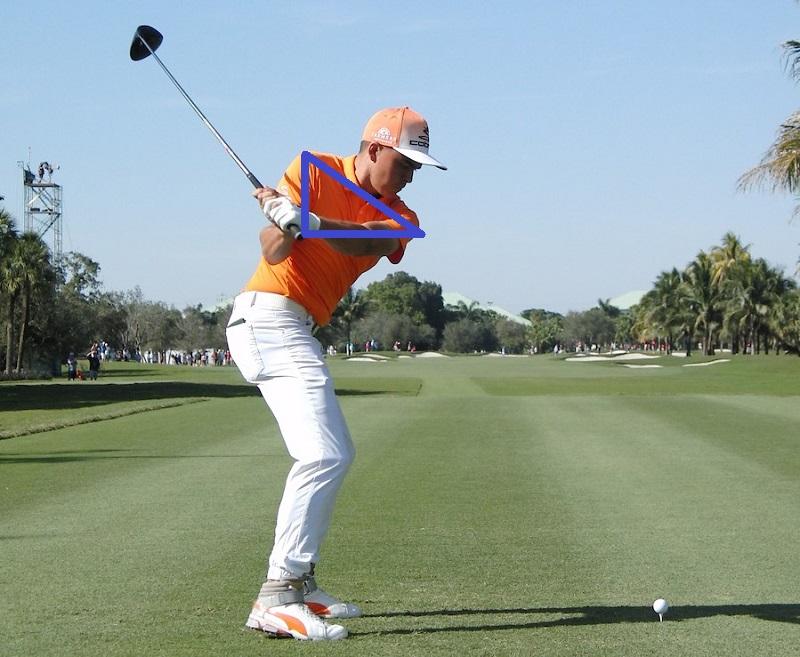 Durant la phase de transition vers le downswing, le club descend derrière le golfeur, et sous son épaule.
