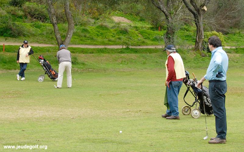 deux joueurs et deux caddies sur le golf d'Estoril au Portugal